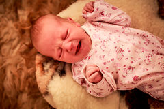 Newborn baby cries on woolen pillow in childish bodysuit Stock Image