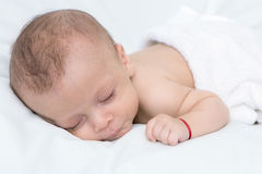 Newborn baby curled up sleeping on a blanket stock images