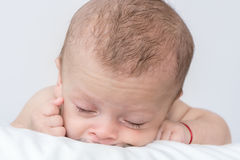 Newborn baby curled up sleeping on a blanket royalty free stock photography