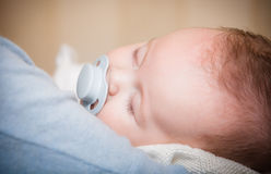 Newborn baby curled up sleeping Stock Images