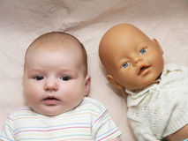 Newborn baby and doll Stock Images