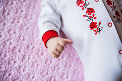 Newborn baby dressed in costume with embroidery Royalty Free Stock Images