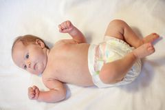 Newborn baby dressed in diaper, lying on a white background Stock Image