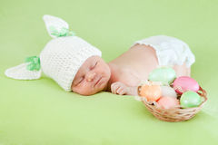 Newborn baby dressed in Easter bunny cap with eggs. Adorable baby dressed in Easter bunny cap with eggs Stock Photo