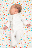 Newborn baby dressed in white sleeping on her back Stock Images