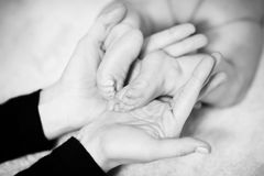 Newborn baby feet in father's hands. Close-up Royalty Free Stock Photography