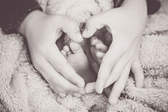 Newborn baby feet with hands of his brother Stock Photo