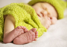 Newborn Baby Feet, New Born Child Sleeping, Kid Foot. Covered by Green Knitted Wool Cloth Royalty Free Stock Images