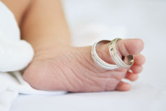 Newborn baby foot. Foot of newborn baby and his parents wedding rings Stock Image