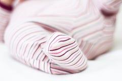 Newborn baby foot in pajamas. stock photo