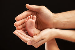 Newborn baby foot in parents hands Stock Image