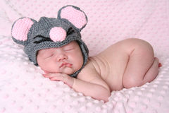 Newborn baby girl. Sleeping wearing a mouse hat