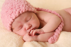 Newborn baby girl. Wearing a pink knitted elf hat royalty free stock photo