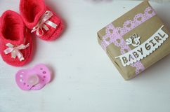 A newborn baby girl background. Newborn accessories for a baby girl on a pink wooden background. stock photography