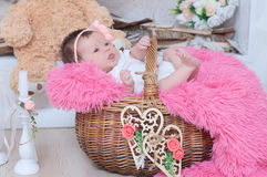 Newborn baby girl in basket,  cute decoration with pink blanket, candles, toy bear and hearts. New child announcement Royalty Free Stock Photos