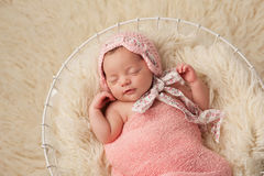 Newborn Baby Girl in Basket Wearing a Pink Bonnet. A portrait of a five week old newborn baby girl wearing a pink bonnet. She has a subtle smile and is Royalty Free Stock Photos
