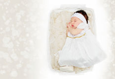 Newborn baby girl in basket wearing white dress Stock Images