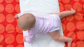 Newborn baby girl on blanket, top view. Cute infant baby lying on her stomach. Babyhood and innocence stock video footage