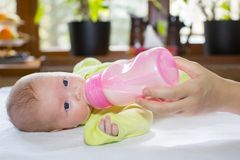 Newborn baby girl with a bottle of milk. Royalty Free Stock Images