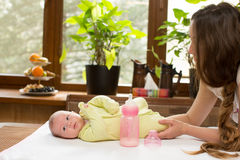 Newborn baby girl with a bottle of milk and mom Stock Photo