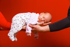 Newborn baby girl in the comfort of moms arms. Parenting family and love concept. one month old baby girl sleeping in the comfort of parents arms, red background Royalty Free Stock Image