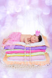 Newborn baby girl in a crown sleeping on the bed of mattresses. Stock Image