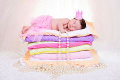 Newborn baby girl in a crown sleeping on the bed of mattresses. Fairy Princess and the Pea Stock Photo
