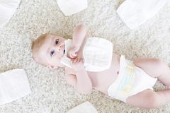 Newborn baby girl with diapers. Dry skin and nursery. Cute adorable newborn baby of 3 moths with diapers. Hapy tiny little girl or boy looking at the camera. Dry stock photography