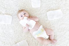 Newborn baby girl with diapers. Dry skin and nursery. Cute adorable newborn baby of 3 moths with diapers. Hapy tiny little girl or boy looking at the camera. Dry royalty free stock image