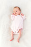 Newborn baby girl on a blanket. Newborn baby girl dressed in a pink body suit, resting on a white blanket. Baby is 11 days old in this photograph. Penty of copy Royalty Free Stock Image