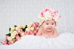 Newborn baby girl in the hat rose smiles. Portrait on a white background Royalty Free Stock Photos