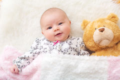 Newborn baby girl on her blanket with her teddy bear Stock Image