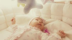 Cute baby girl in her cot Stock Photo