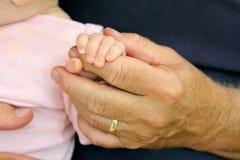 Newborn Baby Girl Holding Grandpa's Hand Stock Image
