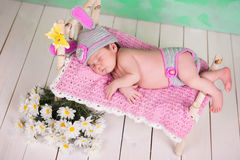 Newborn baby girl in a knitted hare costume sleeping on a wooden crib birch Stock Images