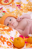Newborn baby girl in orange hat Royalty Free Stock Images