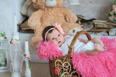Newborn baby girl in pink blanket lying in basket. Cute card composition Royalty Free Stock Photography