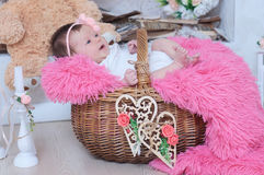 Newborn baby girl in pink blanket lying in basket. Cute card composition stock photos