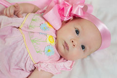 newborn baby girl in pink bow and dress Stock Photos