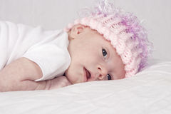 Newborn Baby Girl in Pink Hat. Newborn baby girl in knit pink hat with eyes open stock image