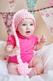 Newborn baby girl in pink knitted hat on the bed.  Royalty Free Stock Photos