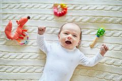 Newborn baby girl playing with colorful toys Stock Photos