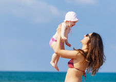 Newborn baby girl playing with mom. Newborn baby girl playing with mom at the beach Royalty Free Stock Photos