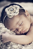 Newborn Baby Girl. Portrait of a mixed race newborn baby girl asleep in blankets with vintage filtered effect Royalty Free Stock Image