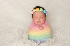 Newborn Baby Girl with Rainbow Colored Swaddle Stock Image