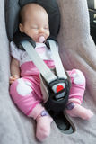 Newborn baby girl sitting in a car seat Stock Images