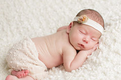 Newborn baby girl in skirt and headband. Baby girl wearing a skirt and headband sleeps peacefully with her hand lying under her face Royalty Free Stock Image
