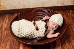 Newborn Baby Girl Sleeping in a Brown Bowl Stock Photography