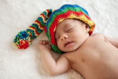 Newborn baby girl sleeping with colorful hat royalty free stock image