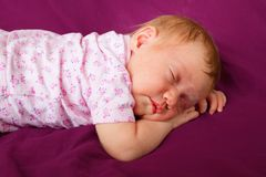 Newborn baby girl sleeping in a cradle. Adorable Newborn baby girl sleeping in bed royalty free stock photography